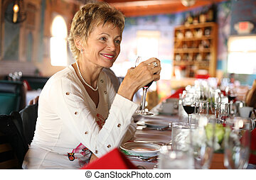 Woman in Italian restaurant - Happy mature woman with glass...