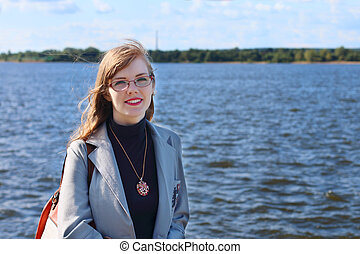 Woman in jacket and glasses stands near river at sunny summer day