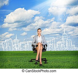 Woman in jacket sits on chair. Background of sketch building, grass