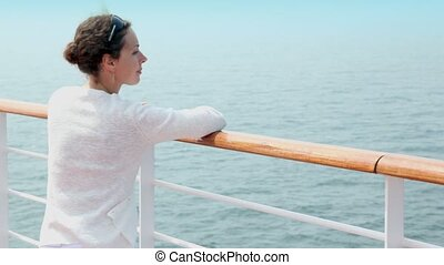 Woman in white jacket stand on deck near fence and watch seascape during cruise