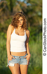 Woman in jeans shorts and a tank top.