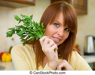 Woman in Kitchen - Beautiful woman in kitchen holding yellow...