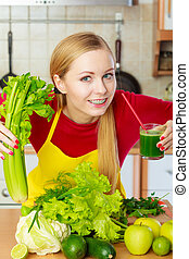 Woman in kitchen holding vegetable smoothie juice
