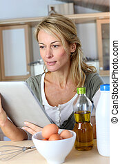 Woman in kitchen looking at dessert recipe on internet