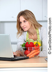 Woman in kitchen looking for cooking recipe