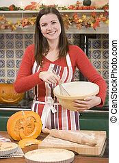 Woman in kitchen making Halloween treats and smiling