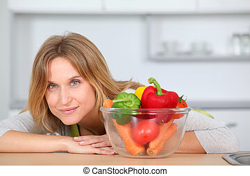 Woman in kitchen ready to prepare meal with vegetables