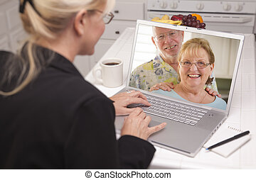 Woman In Kitchen Using Laptop - Online with Senior Couple