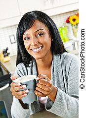 Woman in kitchen with coffee cup