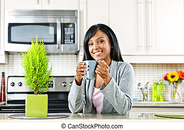 Woman in kitchen with coffee cup - Smiling black woman ...