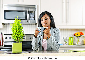Woman in kitchen with coffee cup - Thoughtful black woman ...