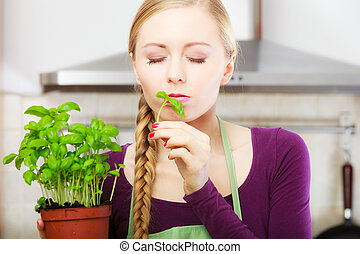 Woman in kitchen with green fresh basil in pot