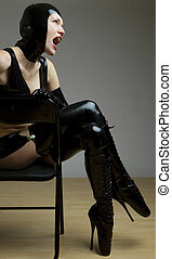 woman in latex sitting on chair