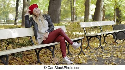 Woman in leather jacket sitting on bench