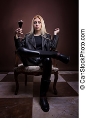Woman in leather jaket sitting on a vintage chair with a glass of liquid in hands studio shot