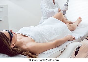 Woman in leg hair removal session with laser device at beauty parlor