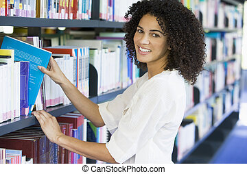 Woman in library pulling a book off a shelf (depth of field)