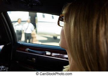 Woman In Limousine At Airport Terminal - Closeup of elegant...