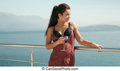 Woman in lingerie holding a glass of red wine on beach.