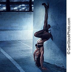 Woman in Lingerie in Upside Down Leaning on Wall