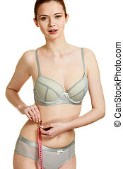 Woman in lingerie measuring her waist with measure tape.