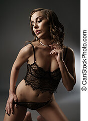 Woman in lingerie posing on dark background