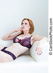 woman in lingerie relaxing on a sofa