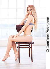 Woman in lingerie. Side view of attractive young blond hair woman in lingerie sitting on the chair and looking at camera