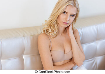 Woman in lingerie sitting on the sofa a