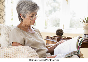 Woman in living room reading book