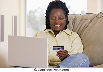 Woman in living room using laptop holding credit card and...