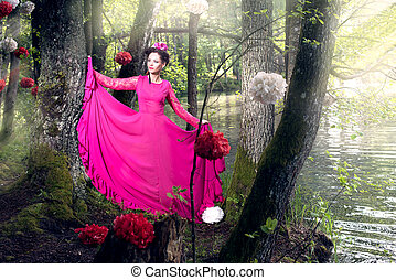 Woman in long pink dress in the wood