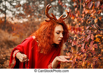 Woman in long red dress with deer horns in autumn forest.