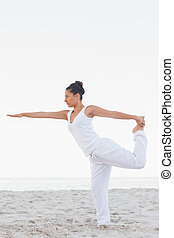 Woman in lord of the dance yoga pose