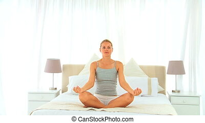 Woman in lotus position in the bedroom