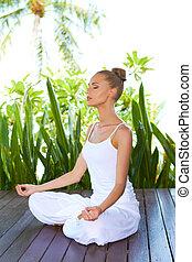 Woman in lotus position meditating - Stylish beautiful woman...