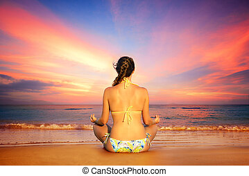 Woman in lotus position on a background of sunset