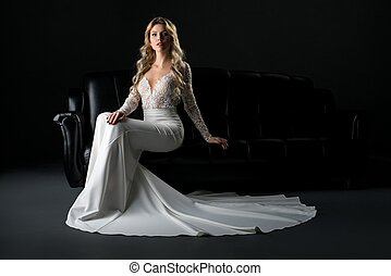 Woman in luxurious lace dress sitting on the sofa