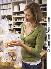 Woman in market looking at cakes smiling