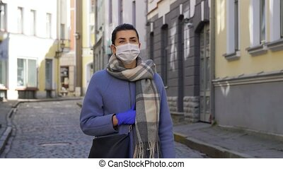 woman in mask and gloves walking in tallinn city - health, ...