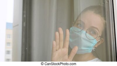 Woman in mask and glasses is missing about her usual normal life on quarantine at home, hospital. Depression in self-isolationg during covid-10 pandemic, epidemic. Portrait of girl looking at window.