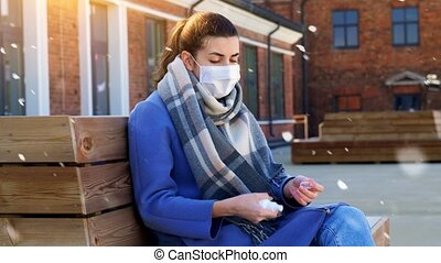 hygiene, health care and safety concept - close up of woman in protective face mask spraying antibacterial hand sanitizer on city street in winter