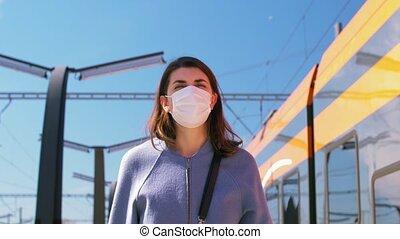 woman in mask walking along railway empty station - health, ...