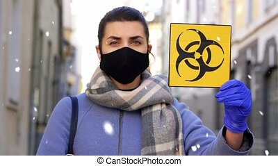 health, safety and pandemic concept - young woman wearing protective medical mask with biohazard sign on city street in winter