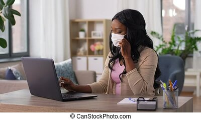 woman in mask with laptop at home office