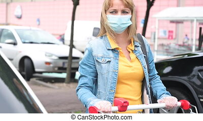 Woman in mask and gloves with shopping cart with purchases in parking lot near supermarket. Outdoors near grocery store. COVID-19 coronavirus.