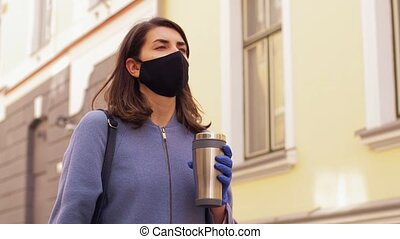 woman in mask with tumbler walking in city