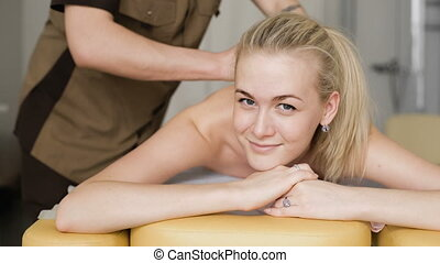 Woman in massage. Young attractive girl smiling with a massage.
