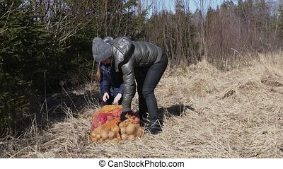 Woman in meadow with potatoes bags for Wildlife animals...