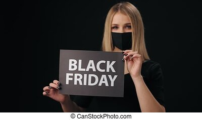 Young woman in black medical mask showing sign with phrase Black Friday while standing in studio. Concept of sales and shopping time.